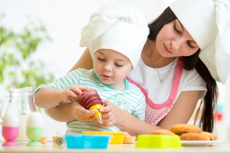 little dough: Mother and kid girl making cookies together