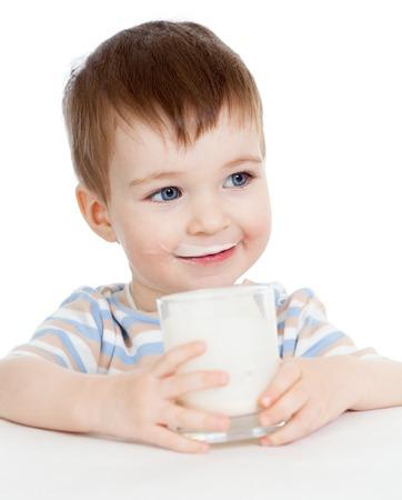 child is sitting: kid boy drinking milk or yogurt from glass isolated