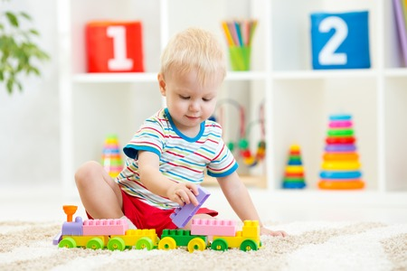 boys toys: kid boy playing with building blocks at home or kindergarten