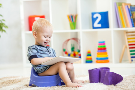 chamber pot: smiling kid sitting on chamber pot playing tablet pc