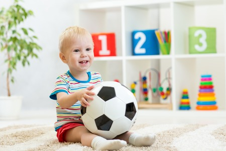 football shoes: smiling kid boy with foot ball  indoor