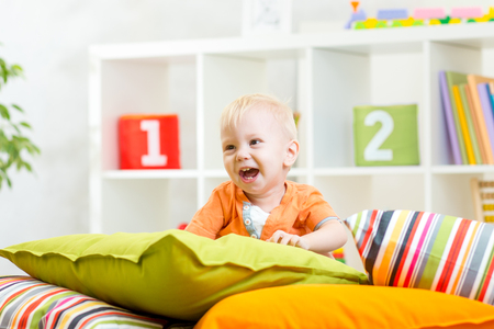 laughing kid boy playing on pillows in bedroom Stock Photo