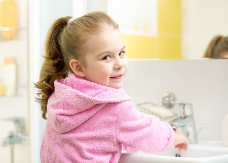 cute kid girl washing hands in bathroom photo