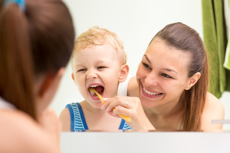 smiling mother teaching kid teeth brushing in bathroom photo