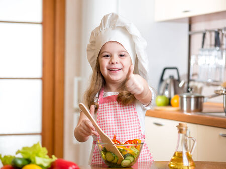 kid girl preparing healthy food and showing thumb up photo