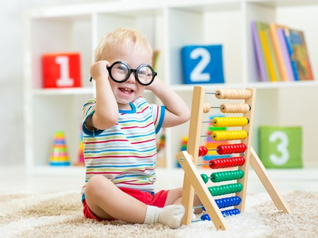 child boy with eyeglasses playing abacus toy indoor photo