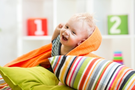 laughing child boy playing on pillows in bedroom