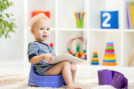 toddler sitting on chamber pot playing tablet pc with toilet paper rolls