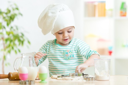 little baker kid girl in chef hat at kitchen Stockfoto