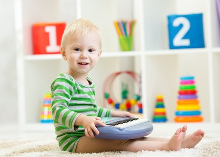 Happy little kid toddler boy having fun playing piano toy sitting on floor in child room photo
