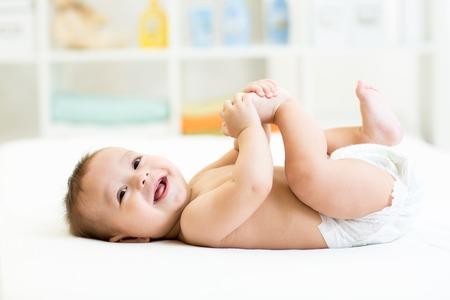 gelukkig baby liggend op wit vel en houdt zijn benen Stockfoto