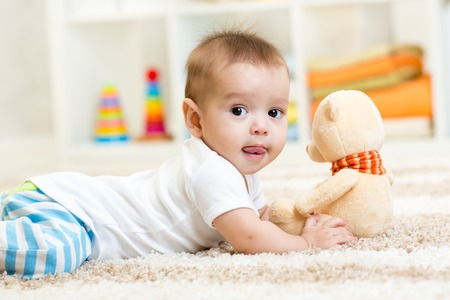 funny baby boy lying with plush toy indoor Stok Fotoğraf