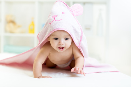 baby towel: baby under the towel after bathing at home