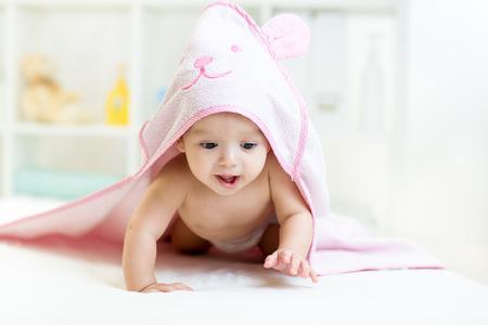 bebe gateando: bebé bajo la toalla después de bañarse en el hogar Foto de archivo