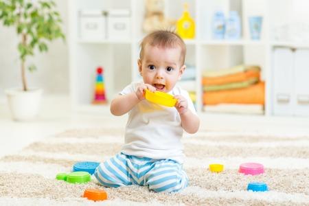 bebe gateando: niño jugando con juguetes en el interior como en casa Foto de archivo