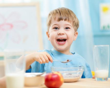 yaourts: enfant de manger des aliments sains à la maison ou à la maternelle Banque d'images