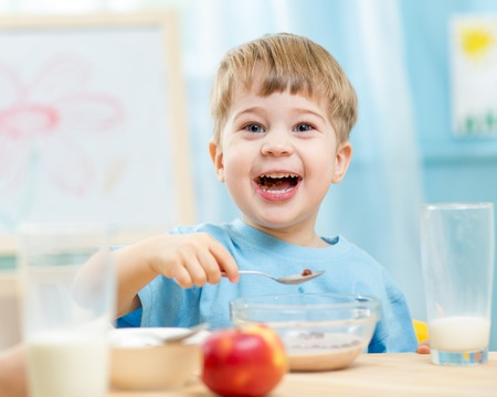 ni�os comiendo: ni�o comer alimentos saludables en el hogar o el jard�n de infantes Foto de archivo