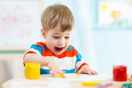 child finger: smiling kid boy painting at home or kindergarten