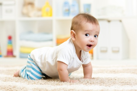 happy baby: crawling funny baby boy indoors at home Stock Photo