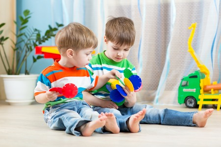 children playing with toys: two kids boys play together with educational toys