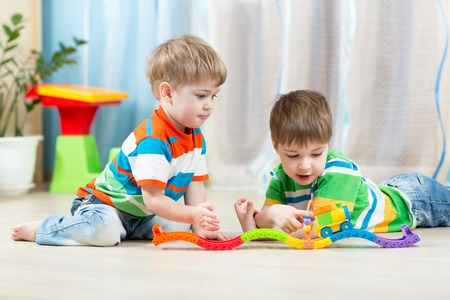 two boys: children  playing rail road toy in playroom