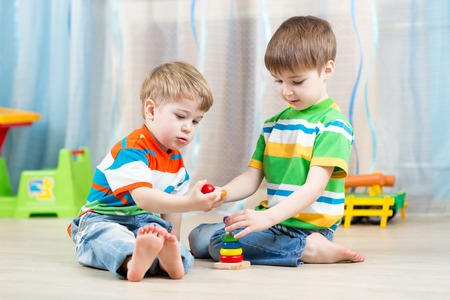 hermanos jugando: niños hermanos que juegan juntos en vivero en casa