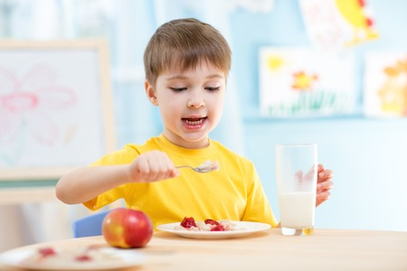 kid boy eating healthy food at home or nursery Stock Photo