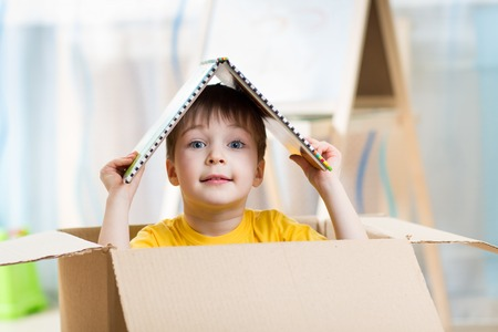cardboard house: kid boy playing in a toy house in children room
