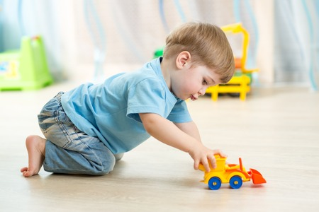 kid boy toddler playing with toy car indoors Standard-Bild