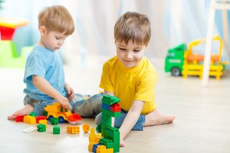 kinderen jongens spelen in de peuterspeelzaal of thuis Stockfoto
