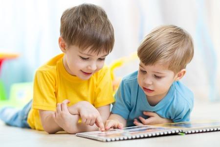 op zoek naar boek in de peuterspeelzaal of kinderdagverblijf twee kinderen Stockfoto