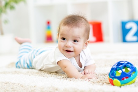 baby boy playing with toy indoors at home