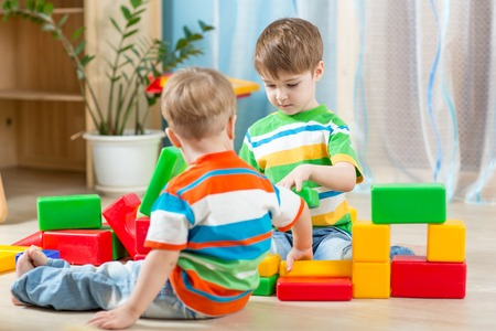 Kids playing block toys in playroom at nursery photo