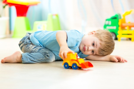 kindergarten toys: child boy toddler playing with toy car indoors