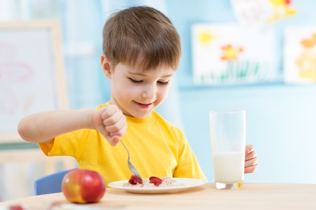 kasha: kid boy eating healthy food at home or kindergarten Stock Photo