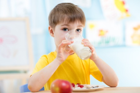 child drinking healthy beverage at home or kindergarten
