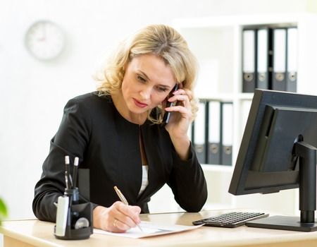 Cute middle-aged businesswoman working at desk in office.