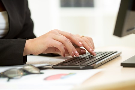 inputting: Close-up of businesswoman hands typing documents on keyboard of computer