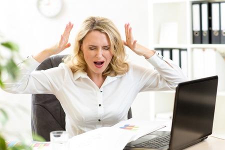 オフィスでラップトップで声高に叫ぶ女性実業家を強調