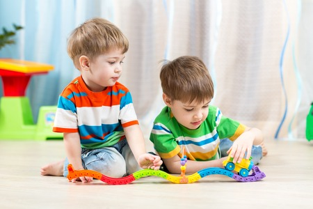 playing: kids playing rail road toy in nursery Stock Photo