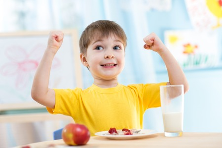 child boy eating healthy food and showing his strength indoors