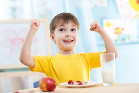 fuerza: muchachos ni�o comer alimentos saludables y que muestra su fuerza en el interior