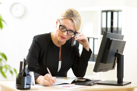 Middle-aged businesswoman working in office. Business lady writing and talking on phone photo