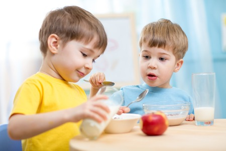 children eating healthy food at home or kindergarten photo