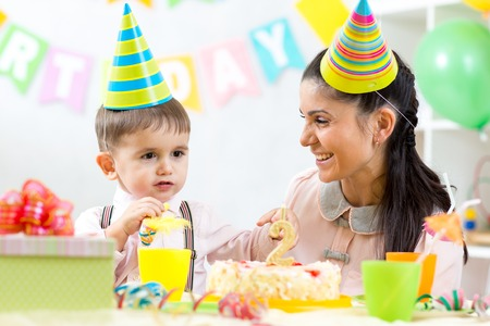 party pastries: Kid boy celebrating his birthday holiday. Mother looking happily to her little son Stock Photo