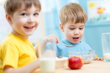 kasha: kids eating healthy food in kindergarten or nursery Stock Photo