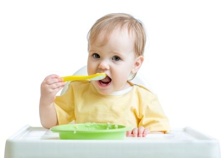 highchair: cheerful happy baby child sitting in chair with a spoon