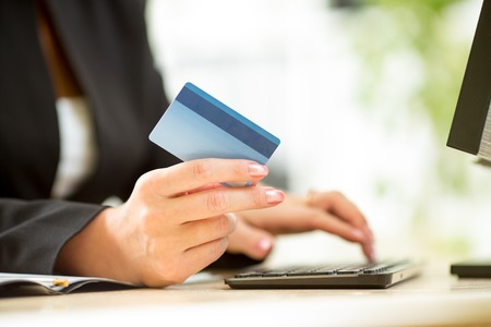 billing: Business woman hands with credit card typing on keyboard Stock Photo