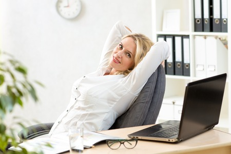 arm chair: senior businesswoman relaxing at work in office
