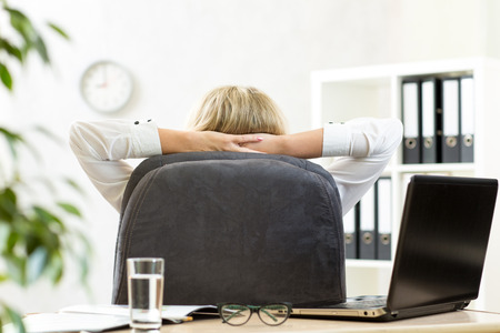 laid back: Businesswoman relaxing in office sitting back in chair with hands behind neck